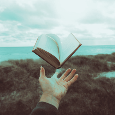 A hand throwing a book away into the unknown